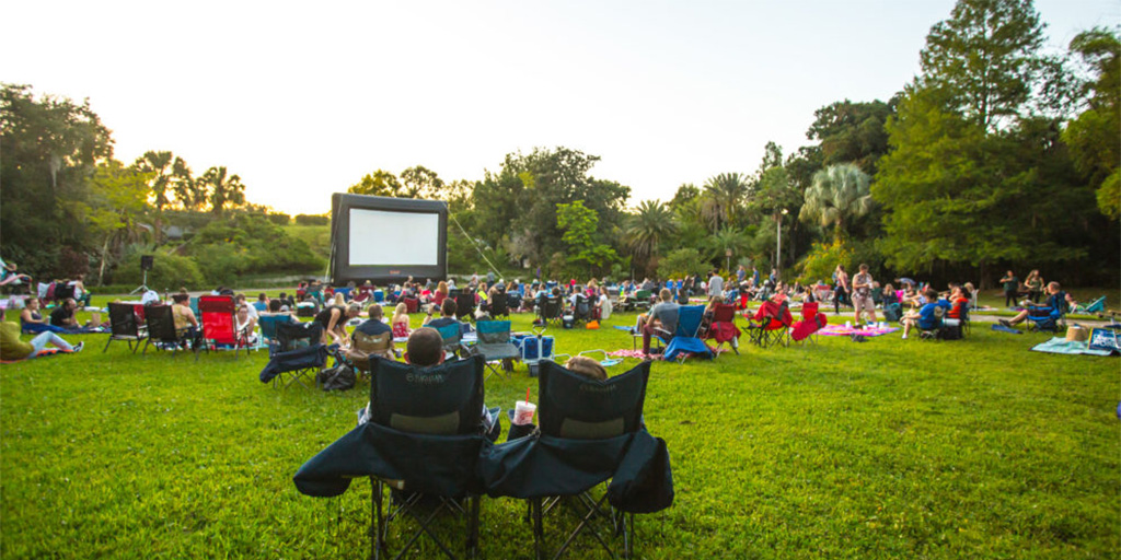 People sitting in chairs waiting for a movie to start at Leu Gardens.